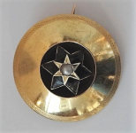 Round golden brooch with star