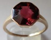 Golden ring with almandin