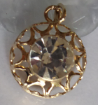 Round gold pendant with clear stones